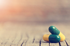 Pharmacy background. Pills on a wooden table. Medicine. Natural background