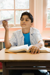 Boy at school desk with paper airplane